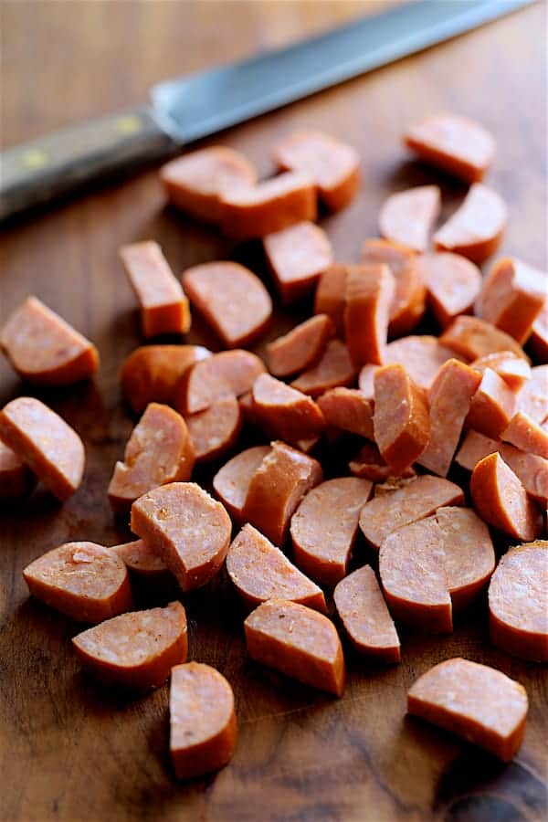 Andouille sausage cut into pieces on wooden cutting board