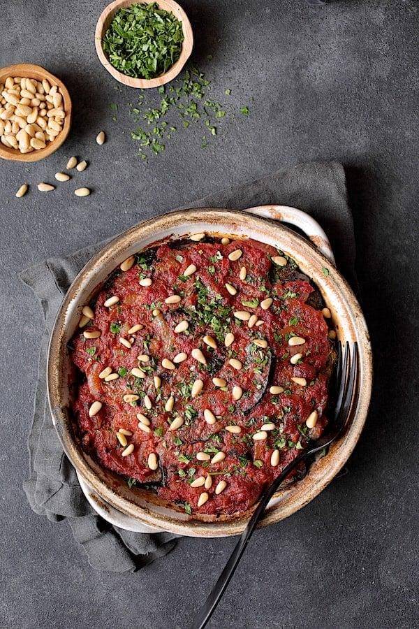 Turkish Eggplant Casserole - Imam Bayildi - Overhead shot of finished, baked dish garnished with pine nuts and chopped parsley