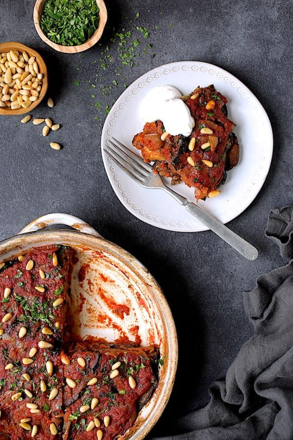 Turkish Eggplant Casserole - Imam Bayildi - Overhead shot of piece on a white plate and baking dish with wedge removed
