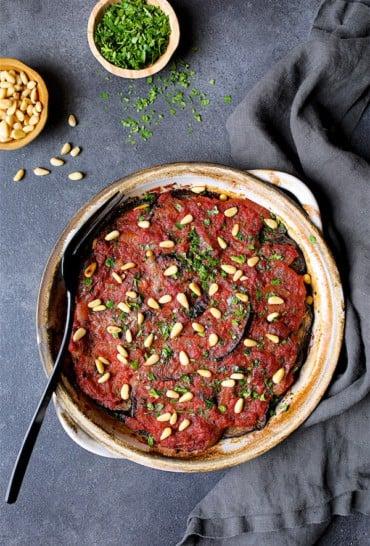 Turkish Eggplant Casserole - Imam Bayildi - Overhead hero shot of dish on dark gray background, gray towel garnished with chopped parsley and pine nuts