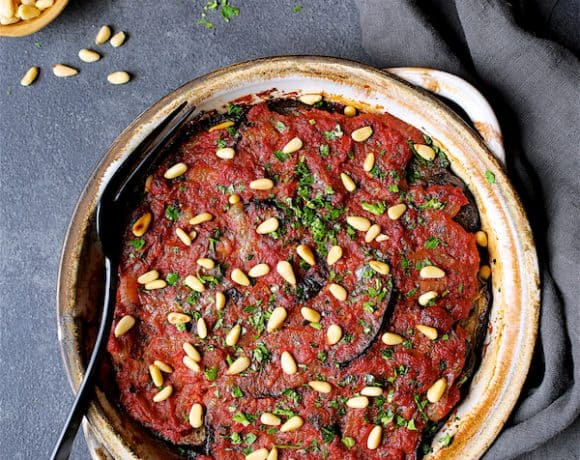 Turkish Eggplant Casserole - Imam Bayildi - Overhead hero shot of dish on dark gray background, gray towel garnished with chopped parsley and pine nuts