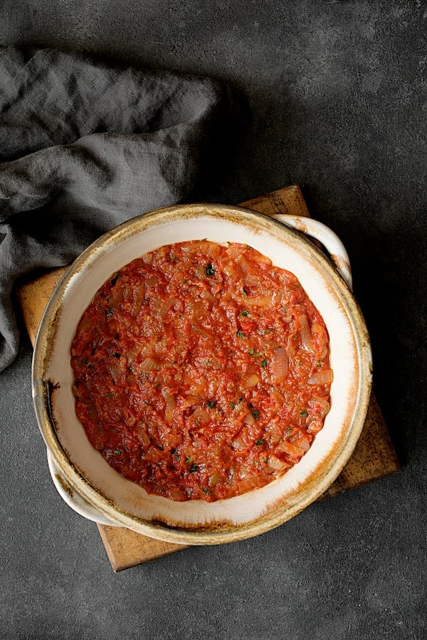 Turkish Eggplant Casserole - Imam Bayildi - Overhead shot of first layer of tomato sauce in baking dish