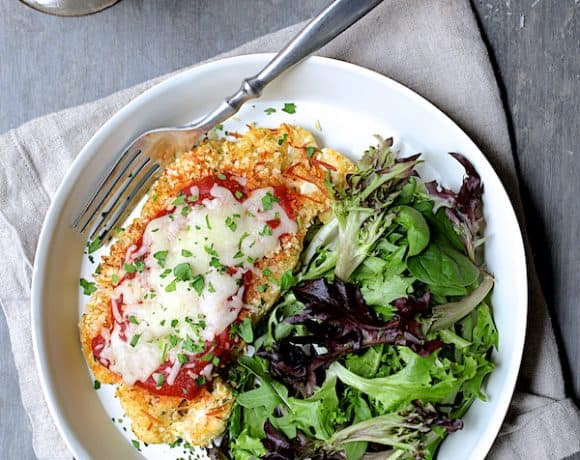 Cauliflower Parmesan - Overhead hero shot on white plate with lettuce greens on the side