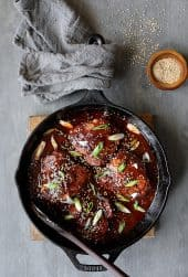 Korean Braised Chicken Thighs - Overhead shot of dish in cast iron skillet garnished with scallion and sesame seeds