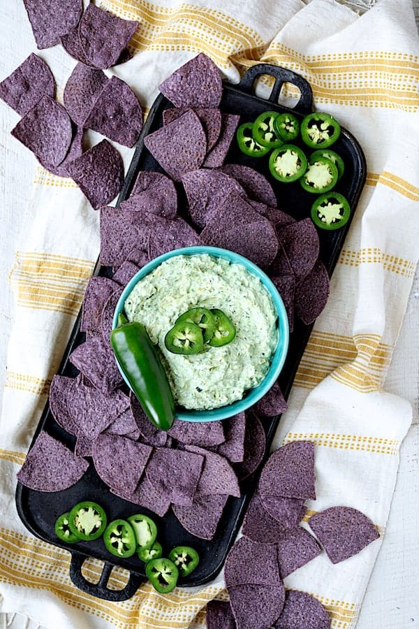 Spinach Artichoke Dip with Fresh Jalapeno - Hero shot of dip on cast iron griddle garnished with fresh jalapeno and blue corn chips scattered around