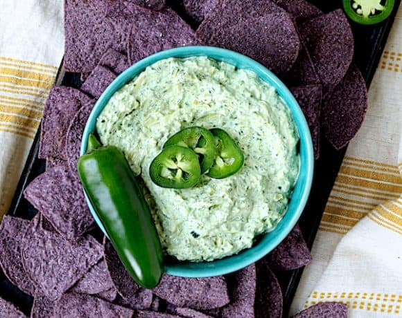 Spinach Artichoke Dip with Fresh Jalapeno - Overhead shot of dip garnished with jalapeno and blue tortilla chips scattered around