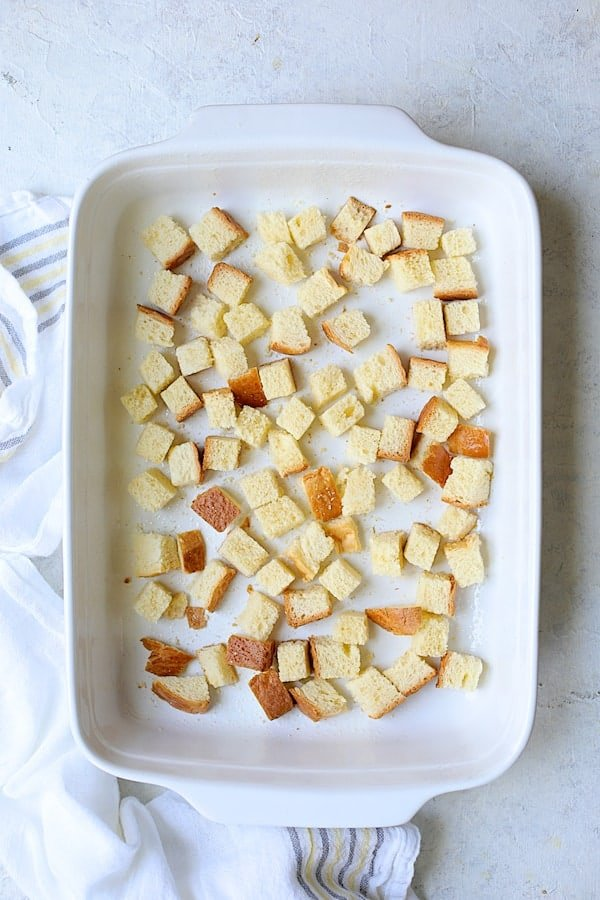 Photo of first layer of brioche in white baking dish for strata.