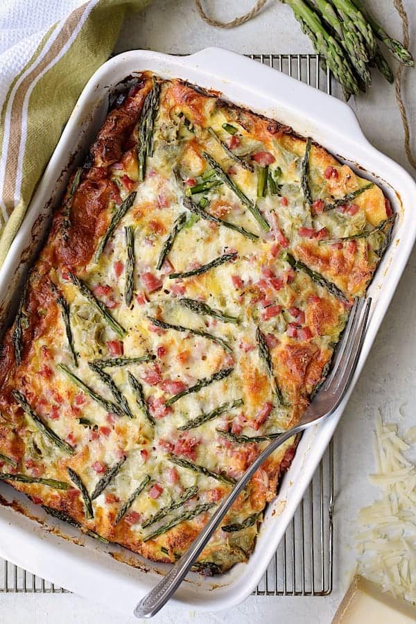 Breakfast Strata with Asparagus, Artichokes, Ham and Gruyere - Close-up shot of baked strata in white baking dish on cooling rack