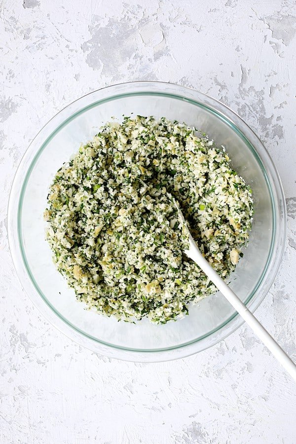 Cauliflower Artichoke Tabbouleh - Overhead shot of salad in glass bowl after ingredients are stirred together