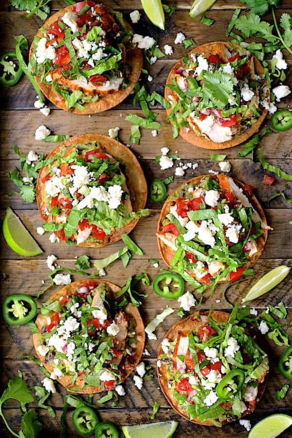 Chicken Tostadas with Black Bean Guacamole and Salsa Fresca - Overhead hero shot on wooden tray
