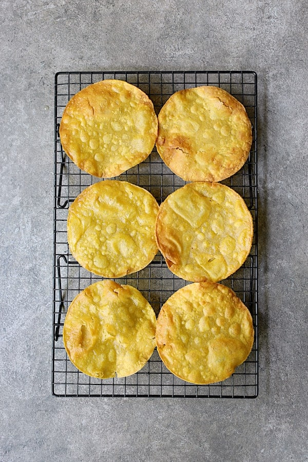 Photo of six tostada shells on cooling rack on gray background.
