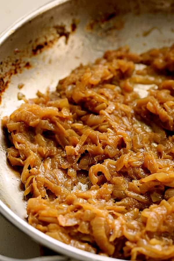 Close-up photo of caramelized onions in stainless steel skillet.