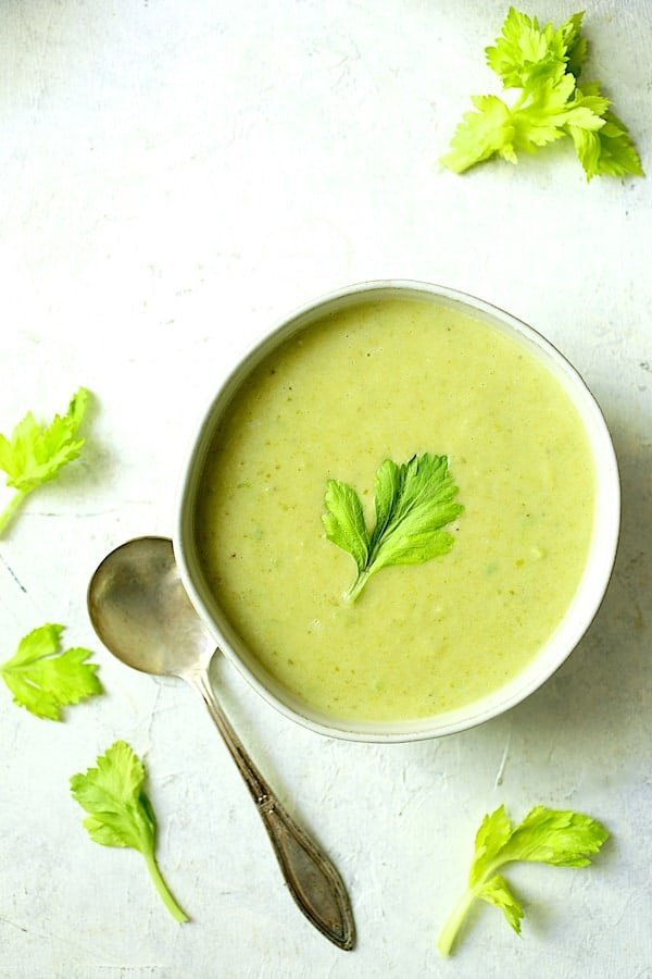 Cream of Celery Leaf and Scallion Soup - Hero overhead shot of single bowl on white background garnished with celery leaves