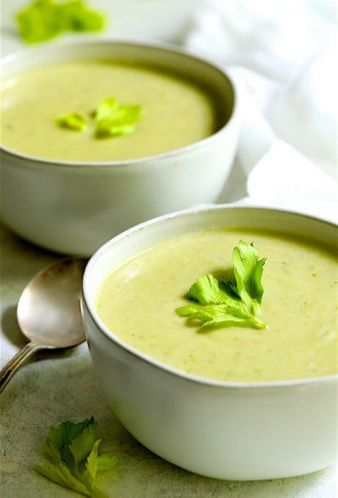 Cream of Celery Leaf and Scallion Soup - Straight-on shot of two bowls of the soup garnished with celery leaves
