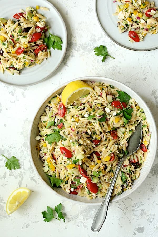 Greek Orzo Pasta Salad - Overhead shot of salad being served onto small white plates