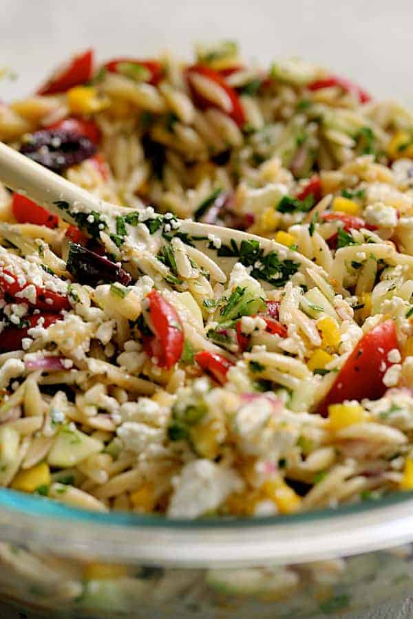 Greek Orzo Pasta Salad - Close-up shot of salad being mixed together