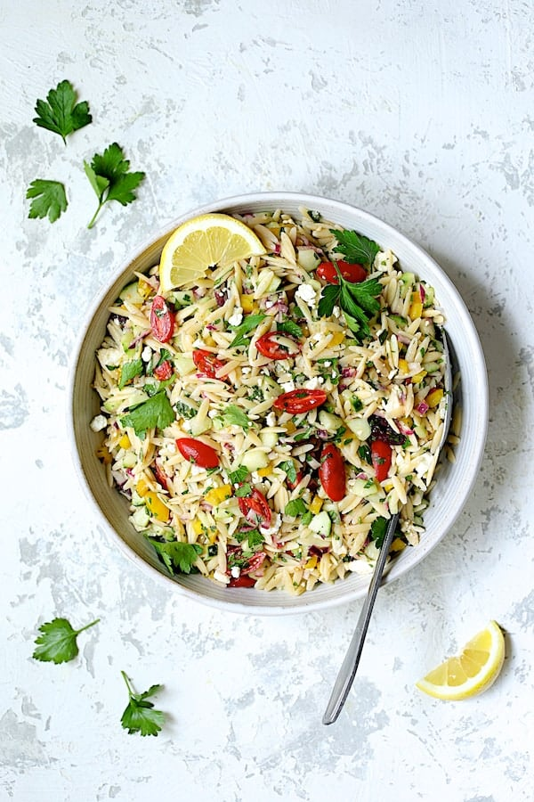 Photo of Greek Orzo Pasta Salad in white serving bowl with serving spoon.