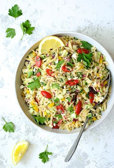Greek Orzo Pasta Salad - Overhead hero shot of salad in white bowl on white distressed background with serving spoon, garnished with parsley and lemon