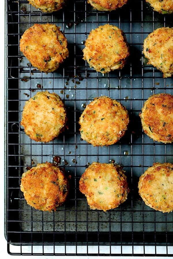 Overhead close-up shot of cooked shrimp cakes on cooling rack set over baking sheet