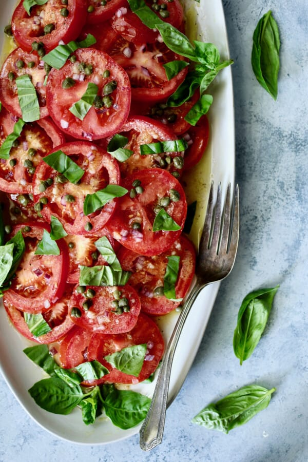 Photo of Easy Fresh Tomato Salad on white platter with serving fork garnished with fresh basil.