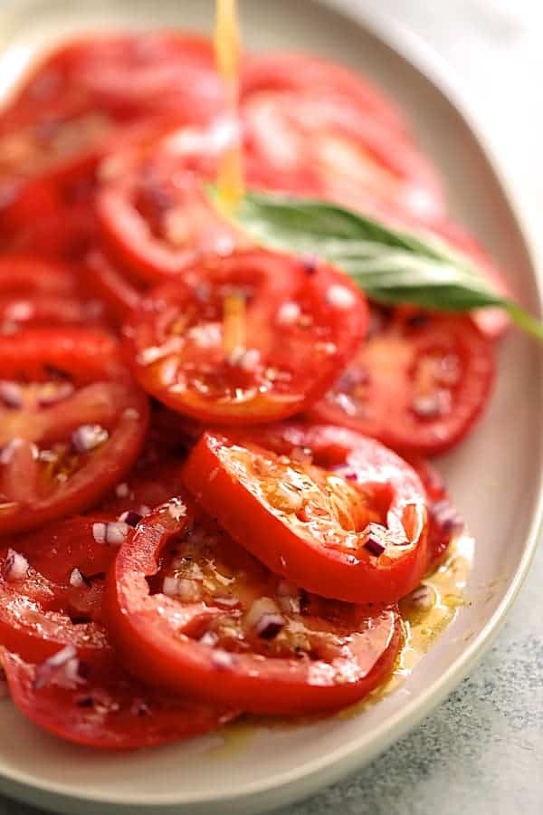 Easy Fresh Tomato Salad - Dressing being drizzled over salad