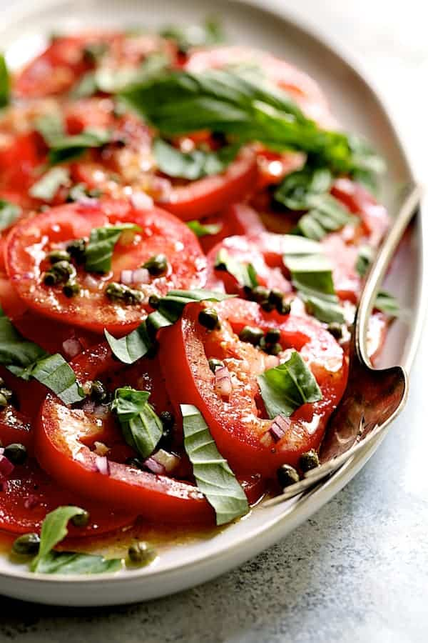 Easy Fresh Tomato Salad - Straight-on shot of salad on white plate with serving fork