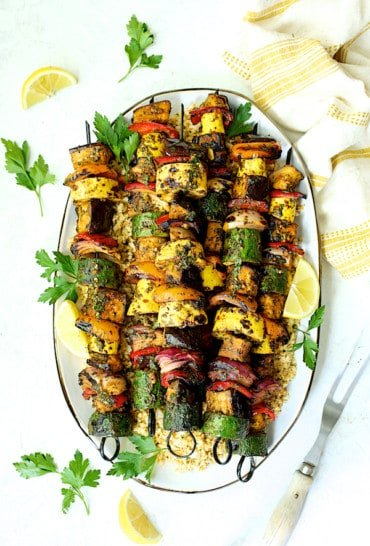 Grilled Vegetable Kabobs with Charmoula - Overhead shot of finished meal on white background garnished with fresh parsley and lemon wedges