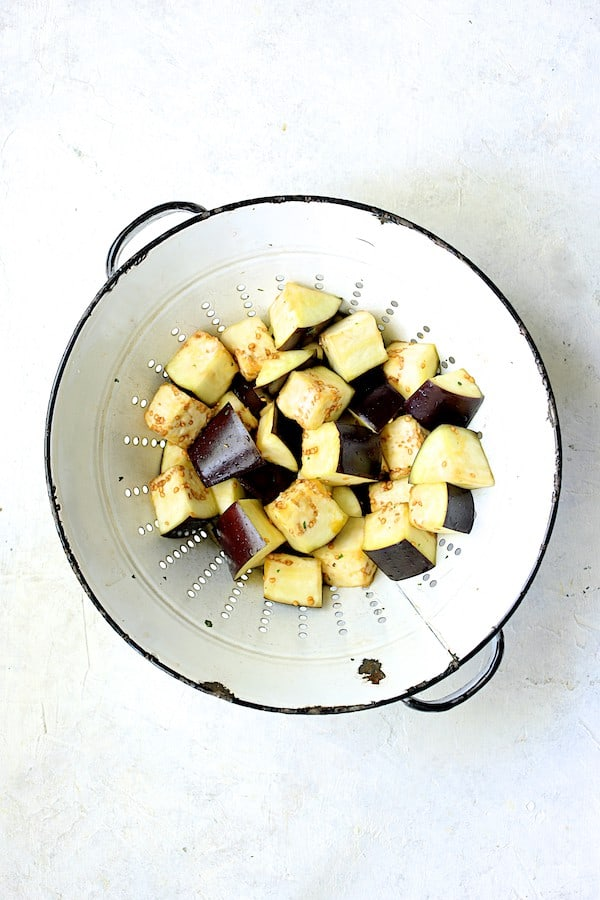 Overhead shot of eggplant cut into cubes in white colander