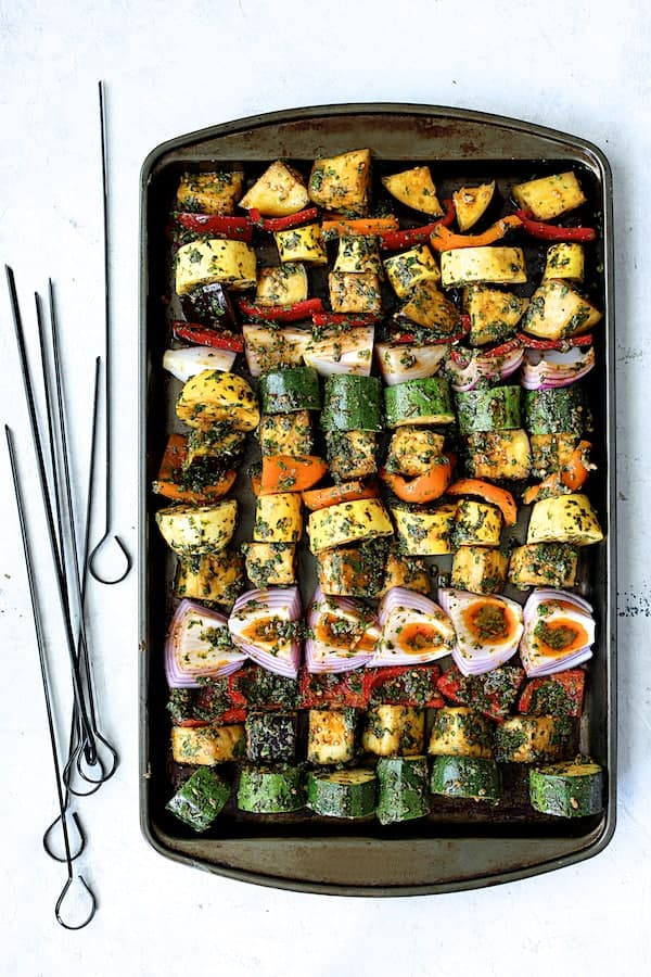 Grilled Vegetable Kabobs with Charmoula - Overhead shot of vegetables arranged on baking sheet before being threaded onto skewers