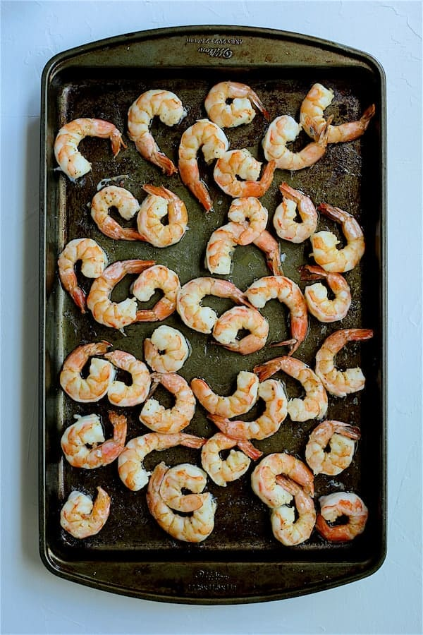 Overhead shot of cooked shrimp on baking sheet