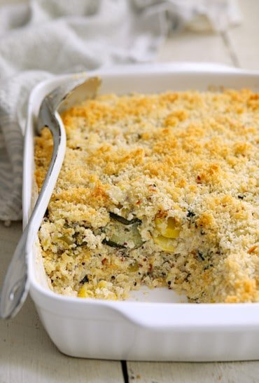 Zucchini, Yellow Squash and Quinoa Casserole - Hero shot of casserole in white baking dish with some removed and serving spoon resting on the side of the dish