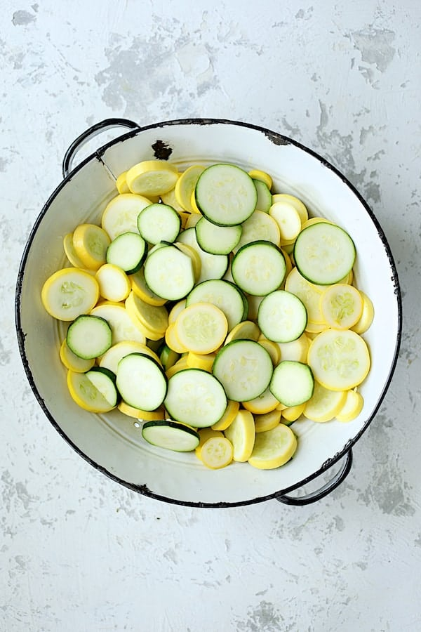 Overhead shot of sliced zucchini and yellow squash in white colander on white background