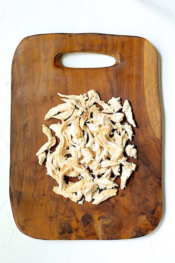 Overhead shot of shredded chicken on rustic wood cutting board