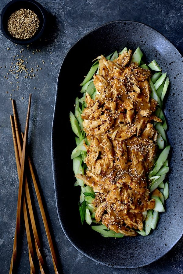 Sichuan Bang Bang Chicken - Overhead hero shot of dish on black oval platter with chopsticks and garnished with sesame seeds