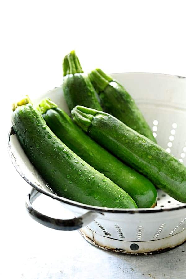 Fresh zucchini in white colander
