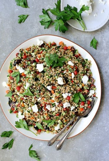 Greek Farro Salad - Overhead hero shot of salad on round platter garnished with parsley