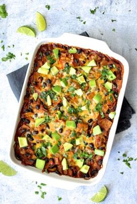 Black Bean and Yellow Squash Enchilada Casserole - Overhead hero shot of casserole in white ceramic baking dish on pale blue background