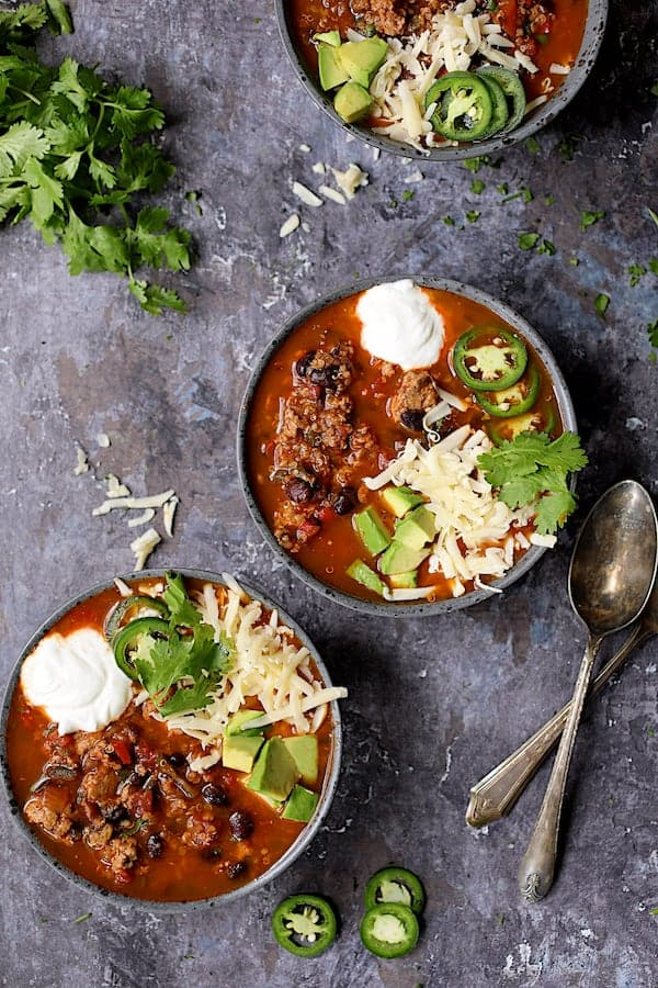 Turkey, Black Bean and Quinoa Chili - Overhead shot three bowls of the chili on gray distressed background garnished with cilantro, jalapeno, cheese and avocado