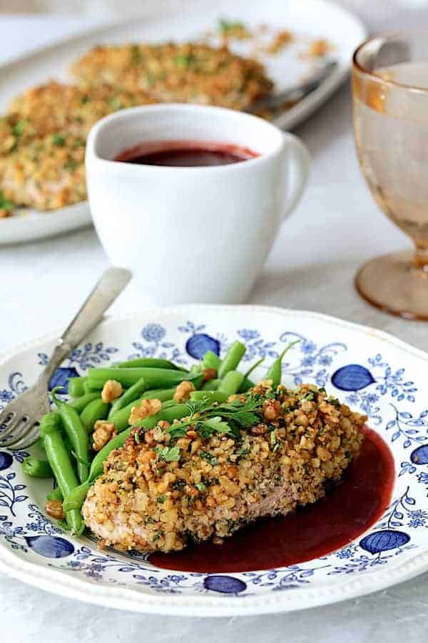 Walnut-Crusted Chicken with Pomegranate Sauce - Close-up straight-on shot of chicken on blue and white plate with green beans