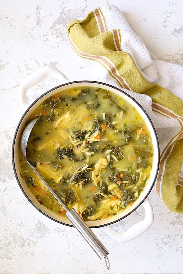 Cold-Fighting Chicken Soup with Kale and Orzo - Overhead shot of soup in white Dutch oven on white background with soup ladle
