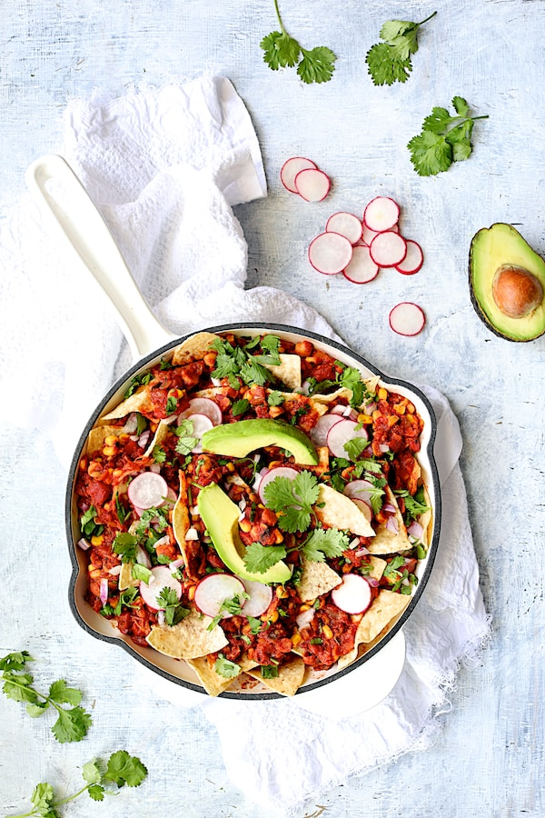 Photo of Skillet Chickpea Chilaquiles in white skillet on pale blue background on white towel with cilantro, radish and avocado.