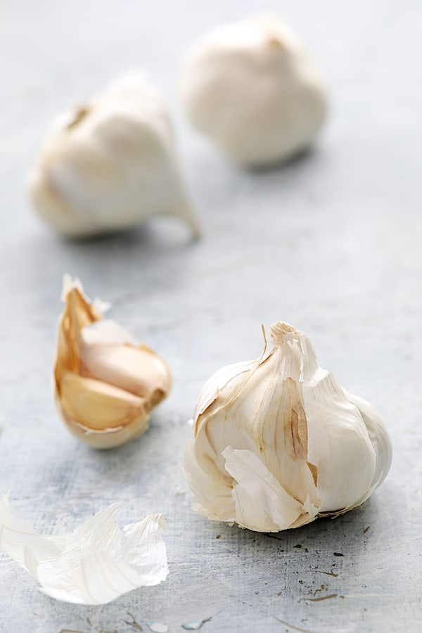 Photo of heads of garlic with some cloves broken away from one.