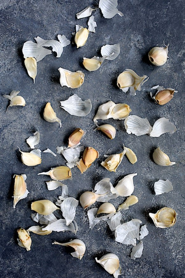Photo of numerous cloves of garlic with papery skins on dark blue background.