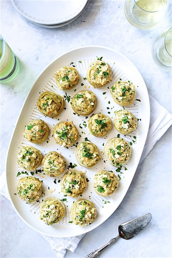 Photo of Deviled Crab-Stuffed Artichoke Bottoms on white oval platter with wine and wine glasses.