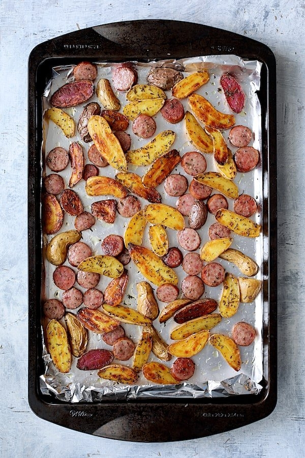 Photo of roasted potatoes and cooked sausage on sheet pan.