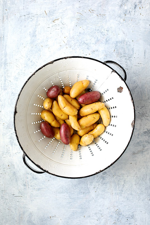 Duck Fat Roasted Fingerling with Sausage - Fingerling potatoes in white vintage colander