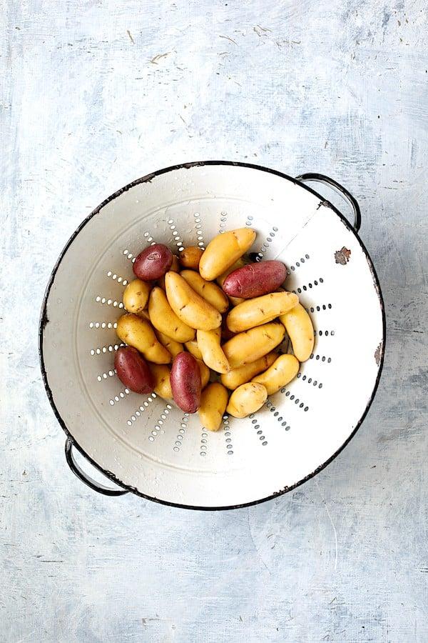 Photo of fingerling potatoes in white vintage colander.