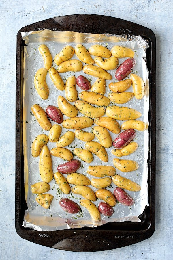 Duck Fat Roasted Fingerling with Sausage - Overhead process shot of halved potatoes on sheet pan ready to be roasted