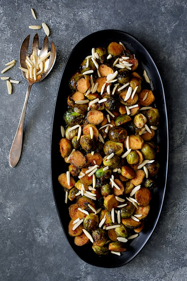 Pan-Roasted Brussels Sprouts with Thai Sweet Chili Orange Glaze - Overhead shot of sprouts on black serving platter with almonds scattered over