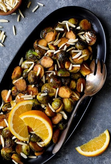 Pan-Roasted Brussels Sprouts with Thai Sweet Chili Orange Glaze - Close-up hero shot of dish on black platter with serving fork garnished with almonds and orange wedges